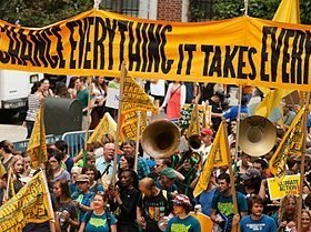 "Sign that says ""to change everything it takes everyone"" carried by crowd in a march"
