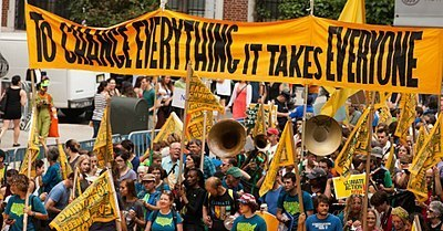 """Sign that says """"to change everything it takes everyone"""" carried by crowd in a march"""