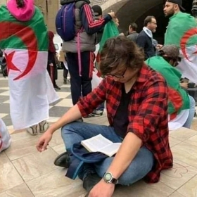 Man seated and reading during Algerian protest