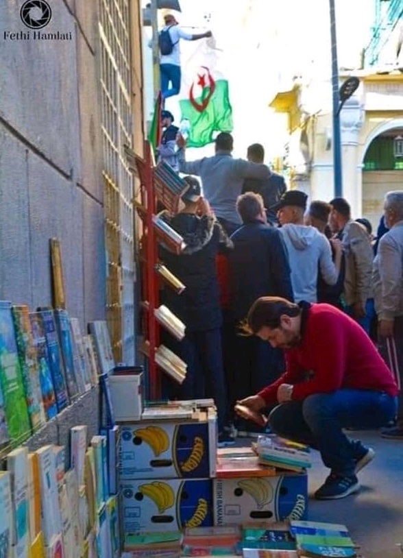 Image of man looking at books during Algerian protest