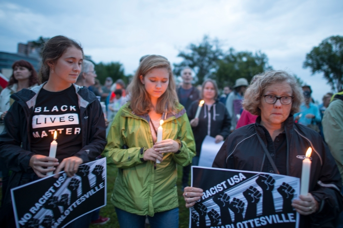 Women holding candles at vigil to show solidarity after Charlottesville incident
