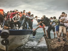 People reaching from boat and from land to help each other