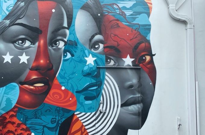Graffiti art of three women, in a Marvel-like style with red, white, and blue.